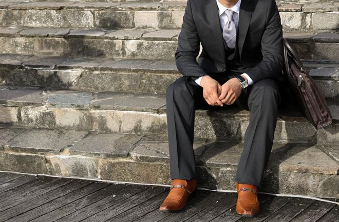 階段に座るスーツの男性