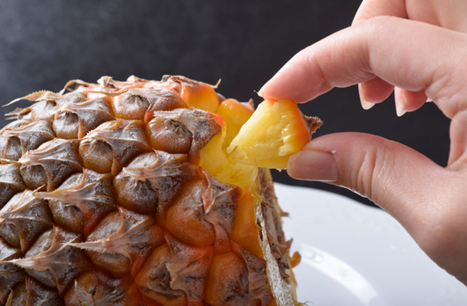 パイナップルの実とつまむ指