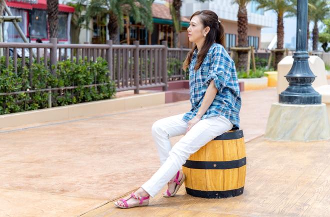 樽の模型に座って景色を眺める女性