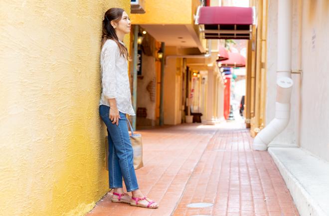 路地で横向きに立つ女性