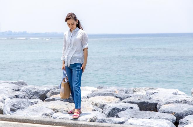 海を背景に立つ女性